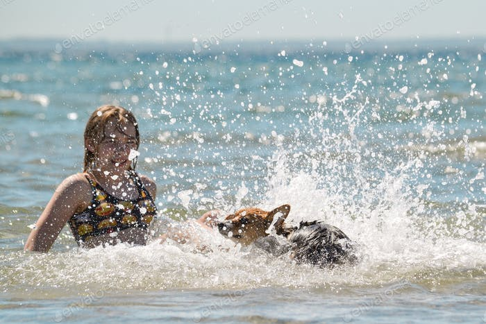 A girl and a dig is playing in the water