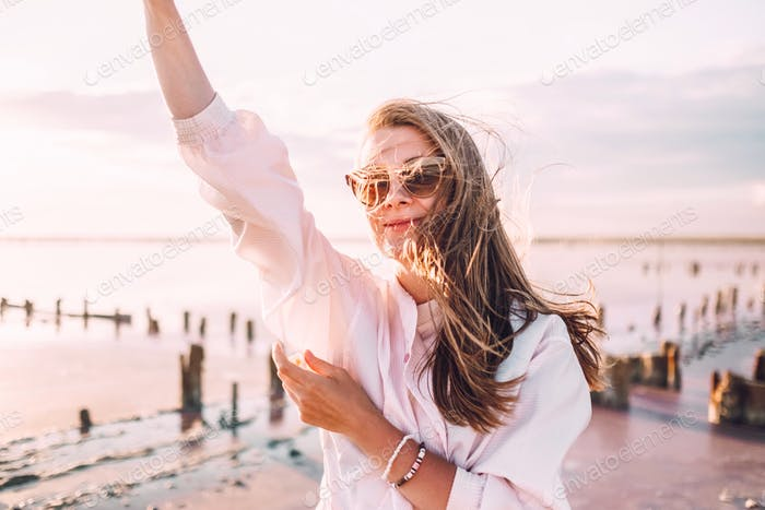Smiling beautiful woman with hair blowing in the wind waving a hand to somebody at the sunset