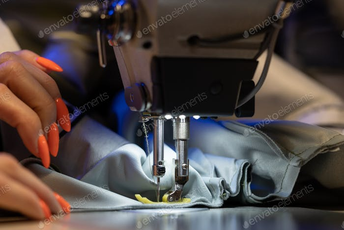 Seamstress work on sewing machine, closeup. Woman fashion designer create new clothes collection