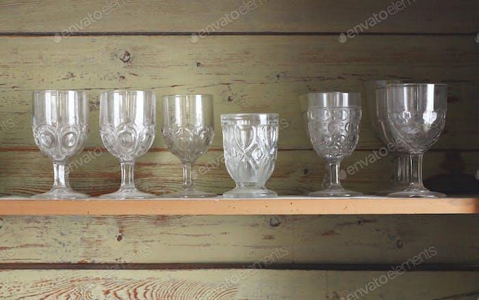Elegant goblet glasses in rustic shelving
