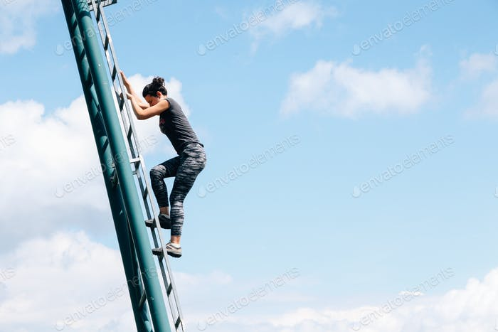 Woman climbing metal ladder on blue sky background. Ambition and determination.