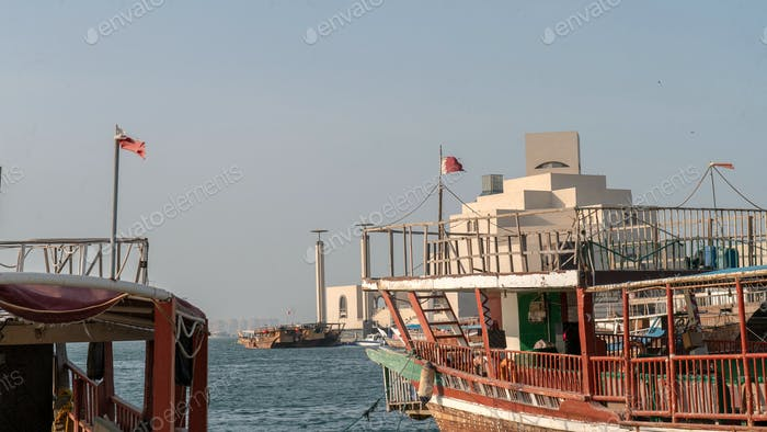Traditional dhow boat at Doha Dhow port with Museum of Islamic Art building in the background