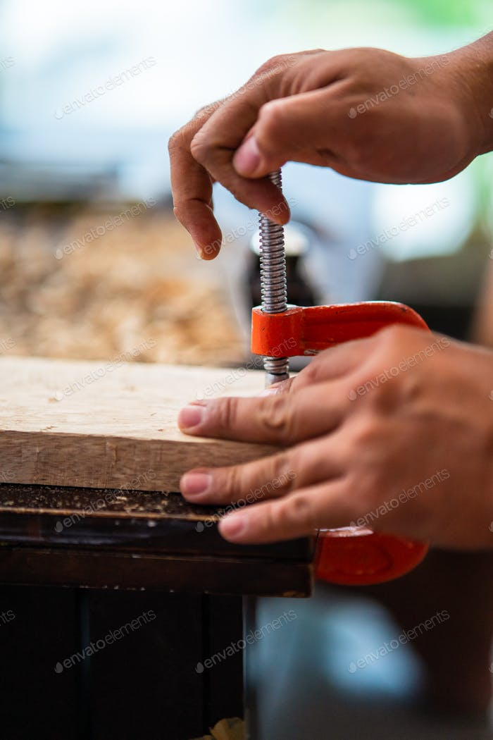 carpenter hand using the C clamp on the wooden plank to the table