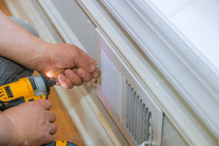 Maintenance repair, man is making the wall vent cover indoor central air conditioning, vents