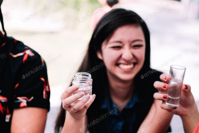 Celebrating life and drinking with friends. A young woman smiling before taking a drink. Cheers to l