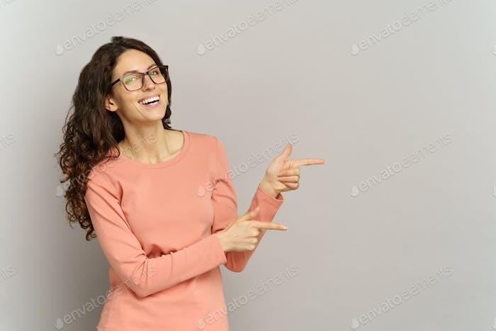 Glückliche Frau zeigen Finger auf den Weltraum über die graue Wand. Studio-Porträt einer Geschäftsfrau zeigt Richtung