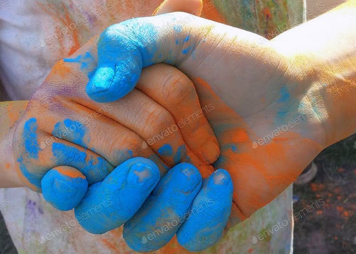 Image of colorful chalk covered hands gripping in unity