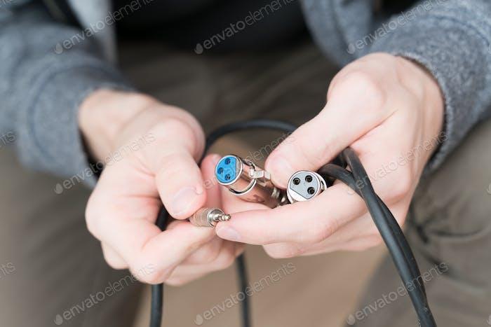 elektrische Leitungen in männlichen Händen
