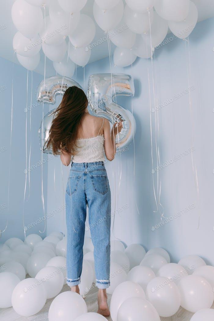 una chica en jeans y una camiseta blanca vacía está celebrando su cumpleaños, 25 años aniversario, mucho o