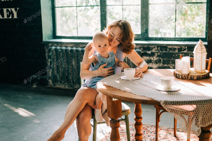 Mom kissing her daughter sitting on the chair at the table and drinking tea or coffee with cup