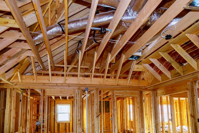Installation under construction with wooden beams of HVAC tubing vents heating system on the roof,