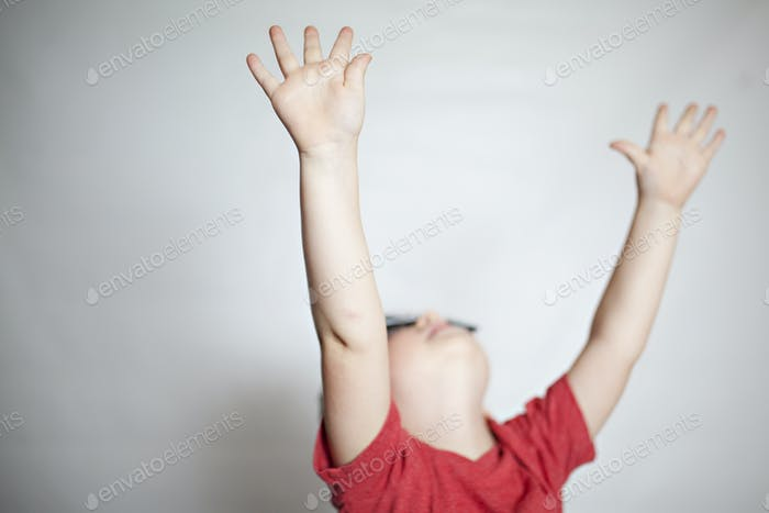 boy with hands raised in the air