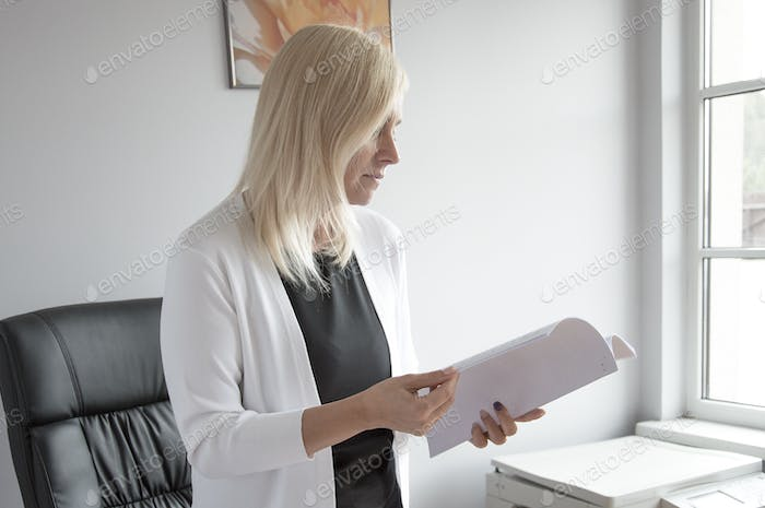 Working in modern offices. Young blond business woman reading and arranging papers in the office in