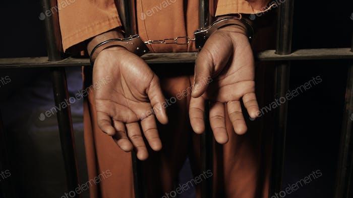 Ein schwarzer Mann in seiner Gefängniszelle gefesselt
