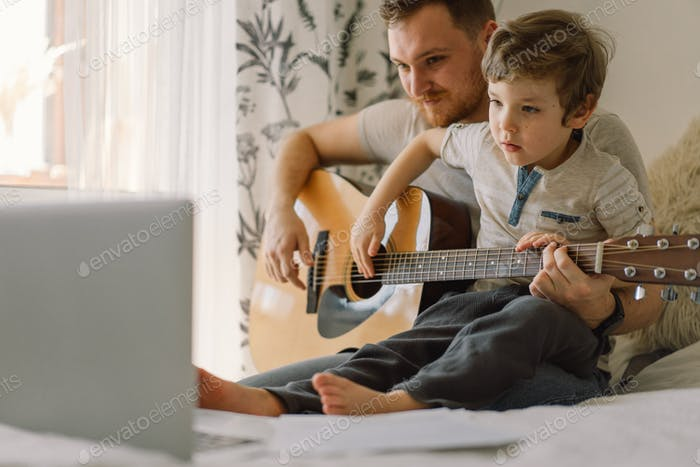Father and son learn to play the acoustic guitar in an online lesson. Happy Father's day.