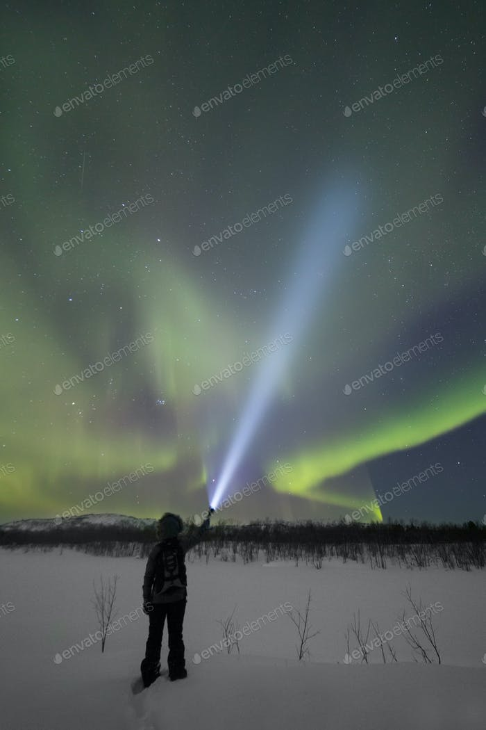 A man shines a powerful flashlight into the sky, illuminated by the northern lights