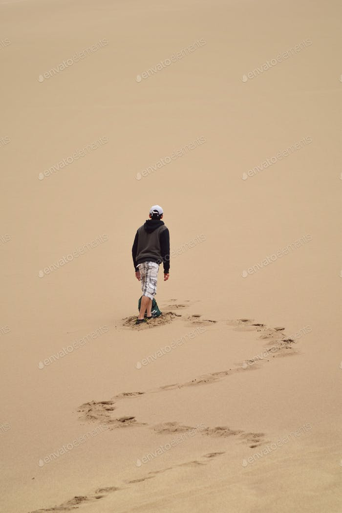 Young millennial explorer adventurer walking on sand dunes on hot day