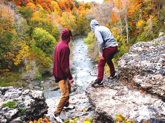 Exploring with friends on a canyon waterfall looking out with fall colors on the trees in the fall