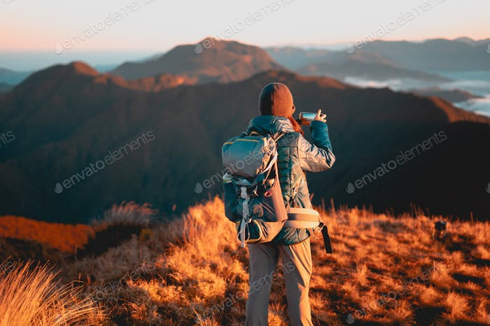 A mountaineer taking the scenic view of the sea of clouds at Mt. Pulag National Park using a mobile