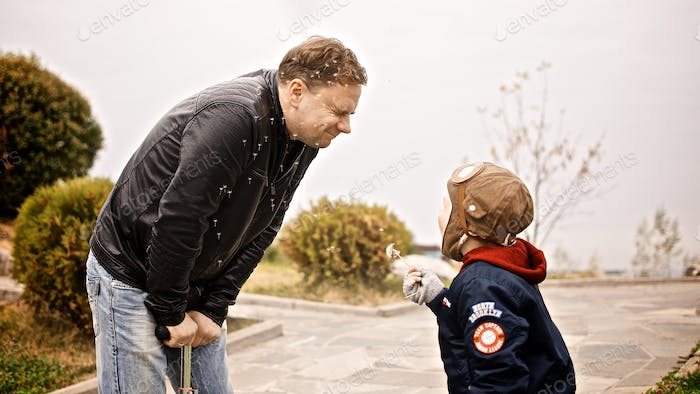 Father and son playing outside with the dandelion