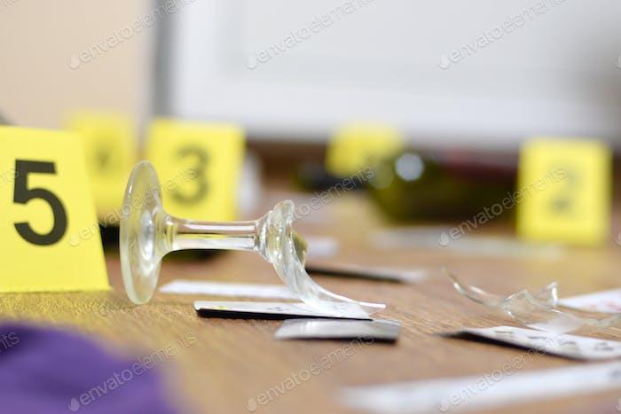Zerbrochenes Glas und eine Flasche Wein, die während der Tatortuntersuchung als Beweis markiert wurde