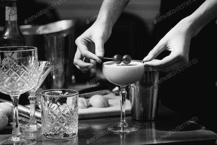 Woman garnishing cocktail at the bar
