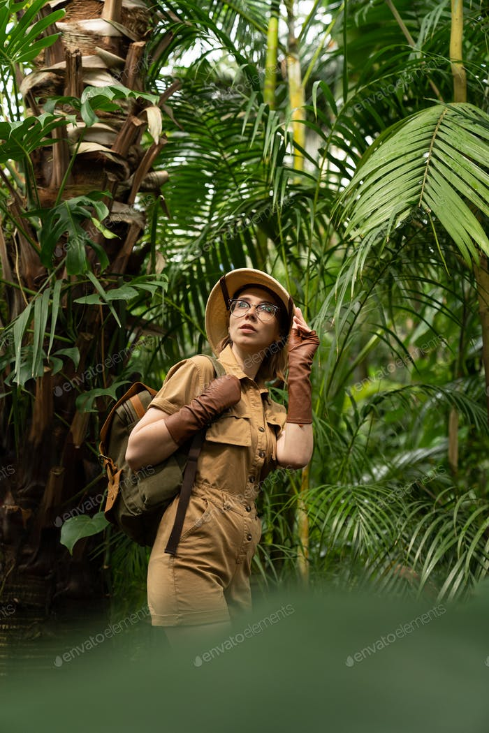 Maturalist or jungle tourist dressed in safary style walks in the rainforest surrounded by palms.