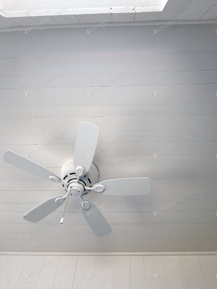 A white ceiling fan in a white clapboard room and ceiling