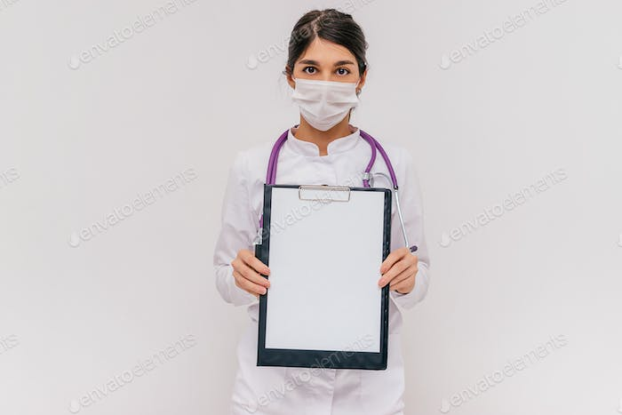 Female doctor holds a clipboard with a blank white sheet.