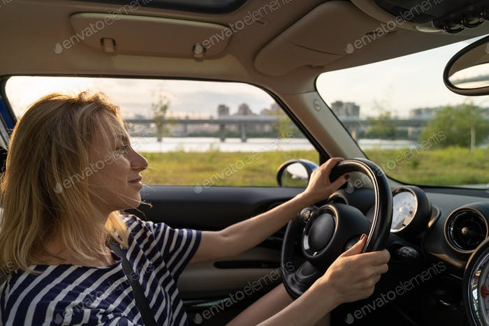 Portrait of carefree European middle woman driving car, smiling, happy during the drive at sunset