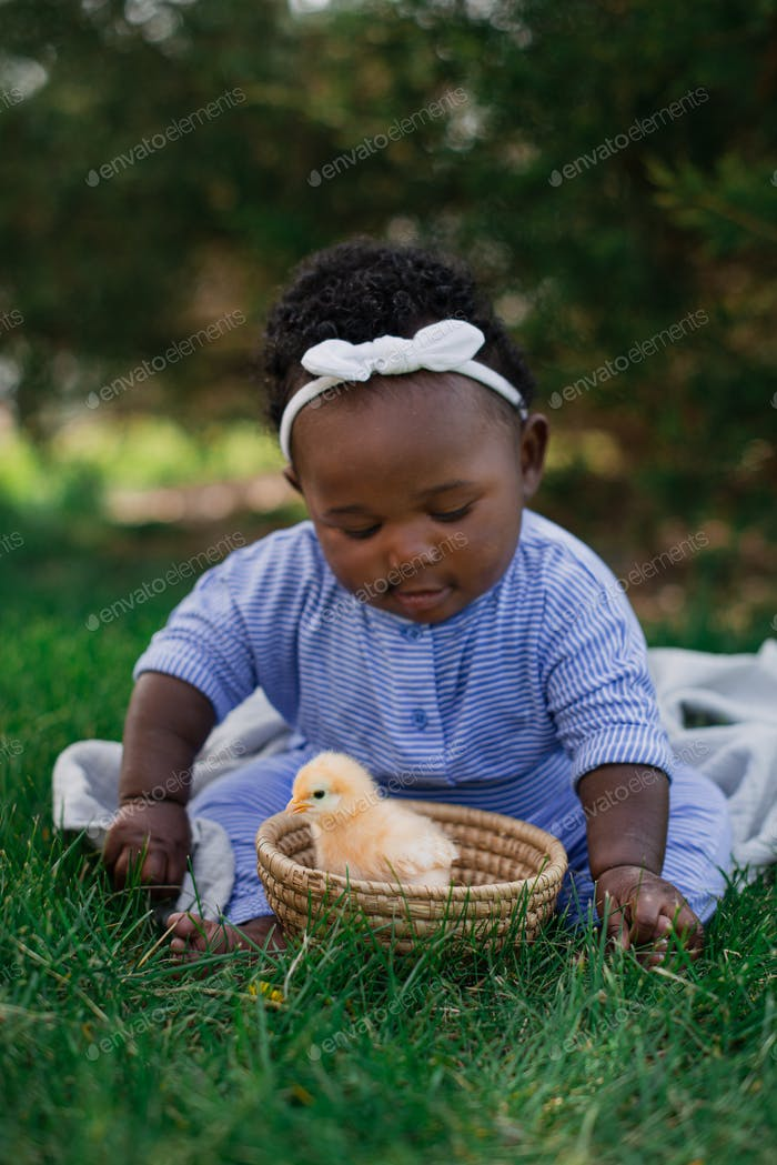 Spring picture of a baby girl and a fuzzy, yellow chick