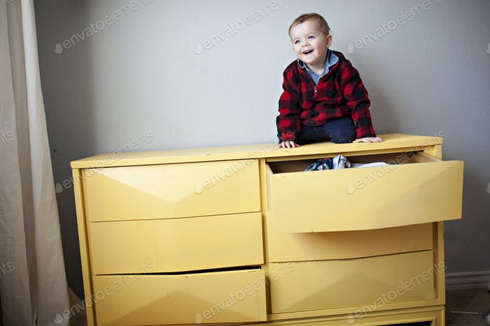 little boy tossing laundry out of a dresser drawer