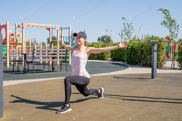 Sportive woman working out on the sports ground in sunny summer day