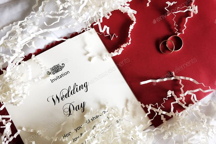 wedding invitation and rings are on a red envelope