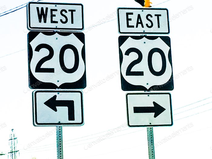 Two 20 20 highway directional double road signs with arrows pointing East and West
