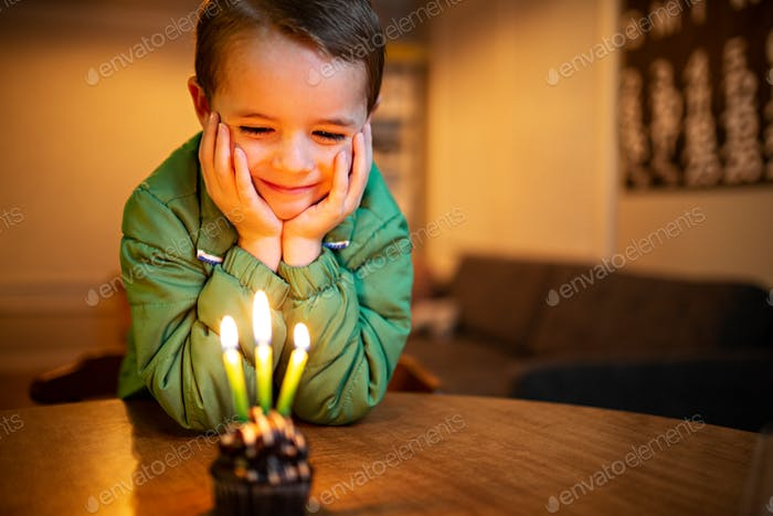 little boy grinning at a birthday cupcake