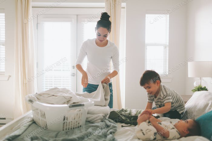 A mother folding laundry with her children in a bright, clean bedroom.