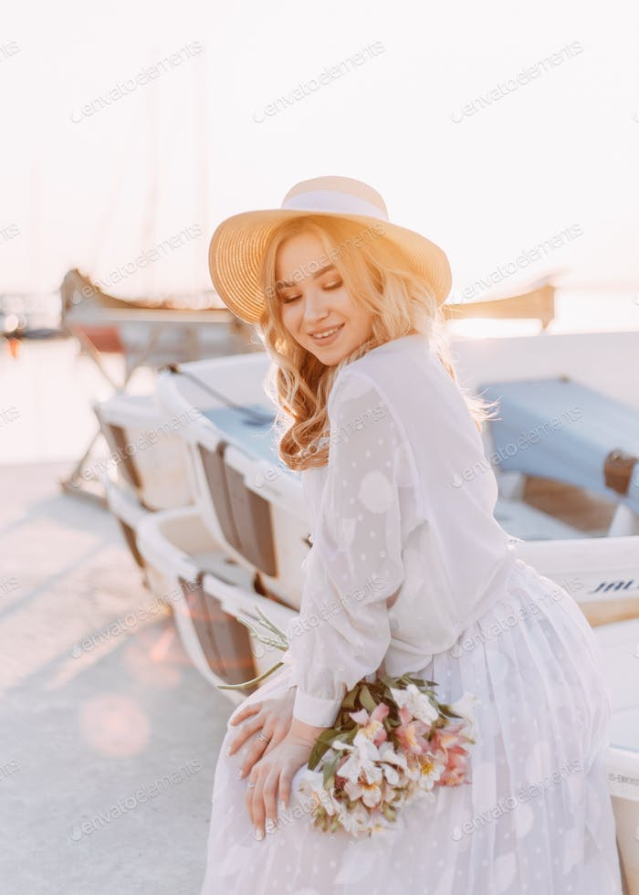 beautiful blonde girl in a white summer dress with a hat with flowers in her hands