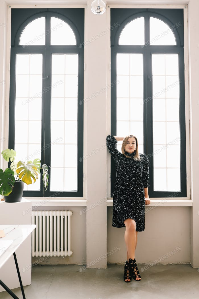 Blonde business lady confident woman in polka dot dress stands and poses in home office