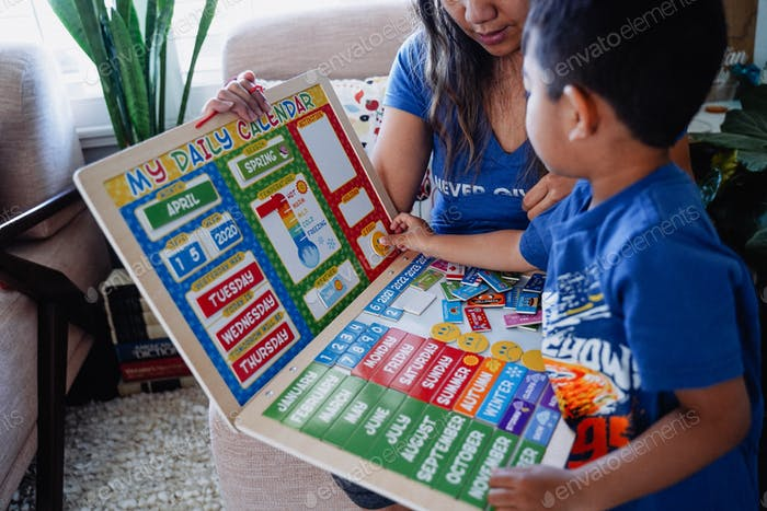 Young diverse boy with mom mother family work from home distance learning class lesson puzzle