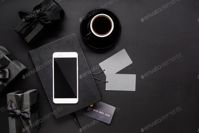 Black smartphone, price tags, coffee and gifts top view on black background
