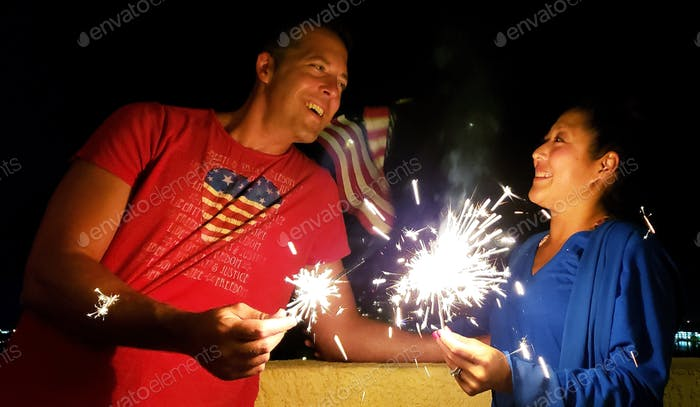 Happy millennial couple playing with sparklers on July 4th with flag in background...