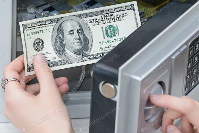 mano de una mujer saca dólares de la caja fuerte