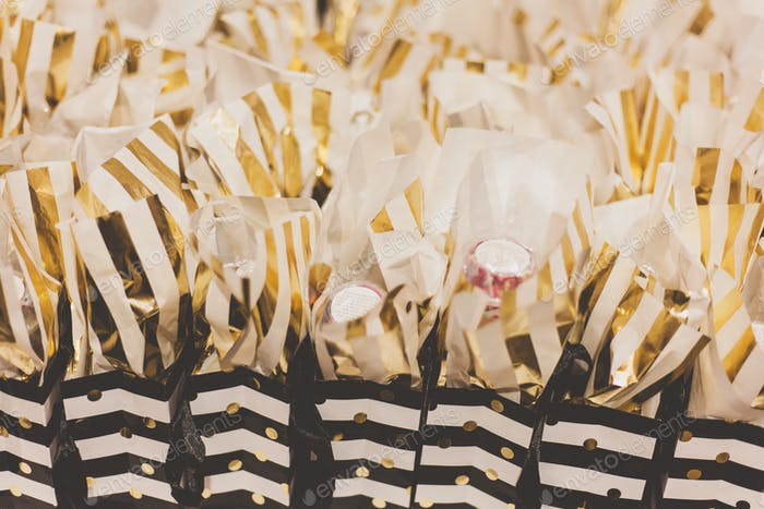 gold striped gift bags filled with party favors on a table