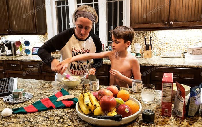 Mother and son bonding while preparing the ingredients of a cheesecake for consumption...