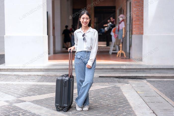 Smiling woman traveller dragging black suitcase luggage bag walking to passenger boarding in airport