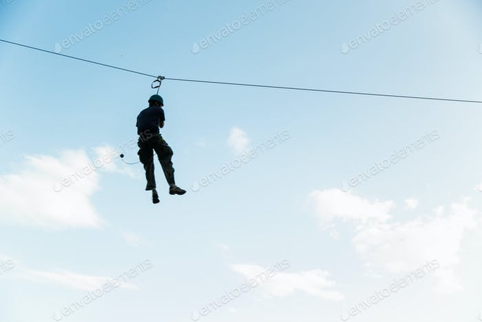 A silhouette of a man on a zip line against a blue sky