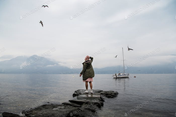 A girl in a green jacket and a pink hat stands with her back on the lake and enjoys the view. Specta