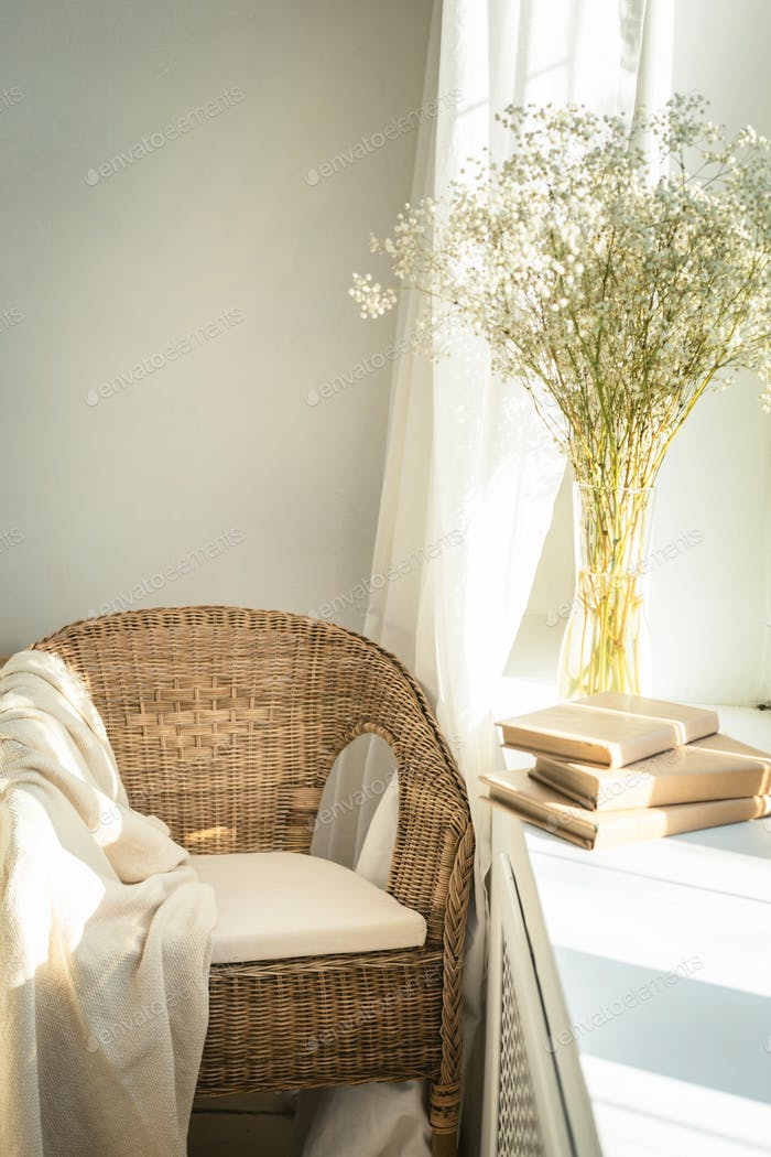 Cozy reading nook by the window with rattan wicker chair