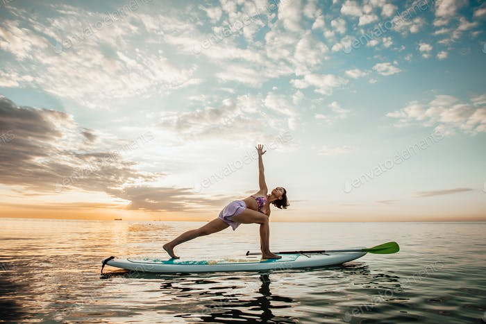 Young woman doing YOGA on a SUP board in the lake at sunrise